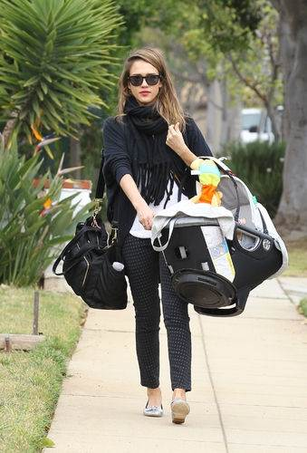 stylish mom carrying car seat with her baby